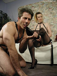 Femdom couple are both wearing BDSM harnesses. He is kneeling? licking her shoes and enjoying the taste of nyloned feet.