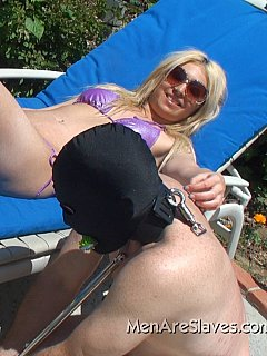 Mistress is enjoying the sunshine in blue bikini while slave is joining her: nude, kneeling, locked into steel shackles and with clamps on his nipples
