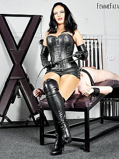 Leather corset, sexy knee-boots and sheer pantyhose is the outfit evil woman is wearing when facesitting a slave, tormenting nipples and penis