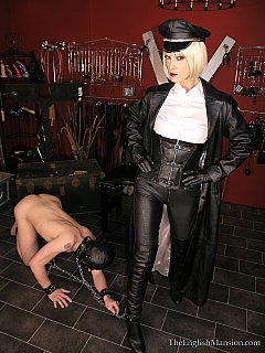 Femdom lady is wearing all-leather military style outfit when training a slave to lick her boots from top to bottom