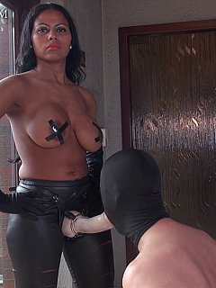 Masked slave is on his knees and blowing big rubber strap-on showing topless dominatrix how well he is trained into a cock-sucker