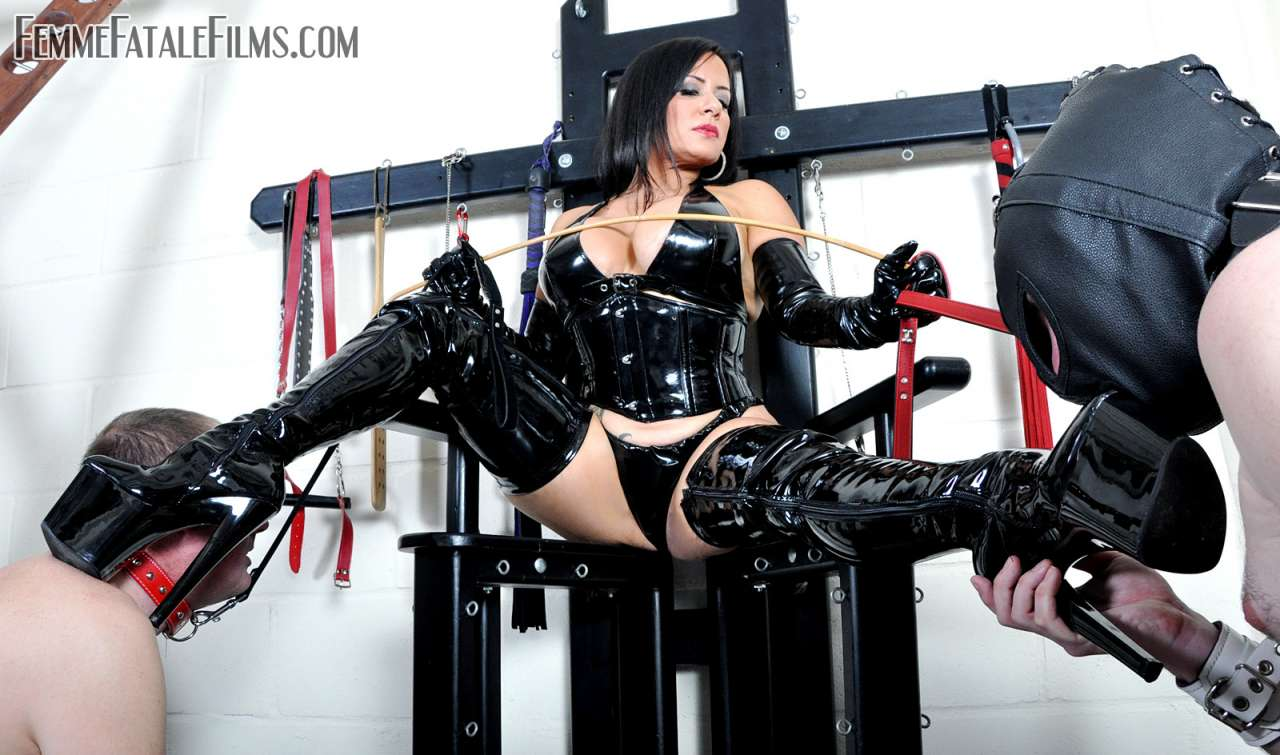 Picture #3 of Curvy MILF dominatrix is wearing shiny PVC fetish outfit in the scene where two slaves are polishing her boots with their tongues