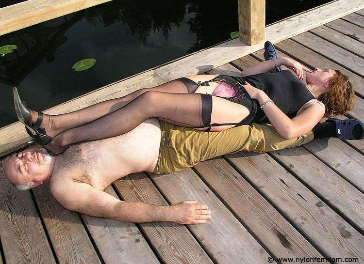Picture #1 of Kinky couple is doing foot worship and trampling outdoors where everybody can see them
