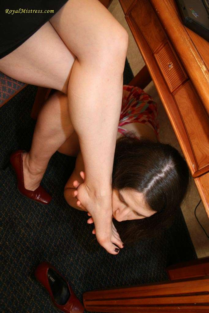 Picture #6 of One girl is working on the computer while another in under the table kissing her feet