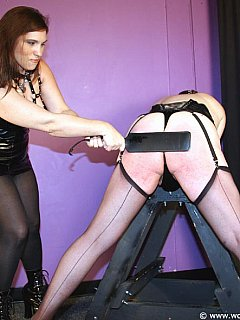 Bent forward in stockings and lingerie is the pose trained sissy is accepting the ass paddling punishment