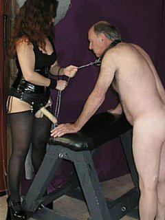 Redhead MILF is dragging her personal anal slave on a leash, bending him forward and plugging big rubber cock into his ass