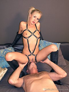 The moments of pleasure when sexy mistress in BDSM harness is sitting on slave face making him lick deep inside her pussy