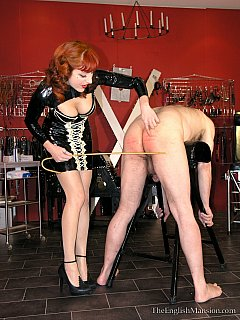 Wooden cane turns out to be powerful training weapon when sexy redhead in rubber dress in using it against femdom slave