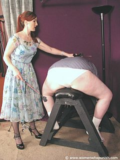 Redhead MILF happen to have a BDSM bench in her basemen which she bends men over and canes their asses