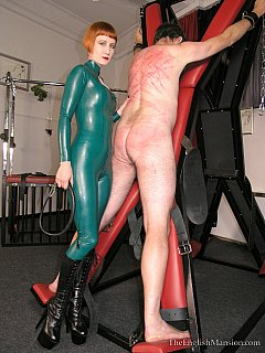 Redhead in rubber is putting her entire strength into whip lashes when educating a naked man strapped to BDSM cross