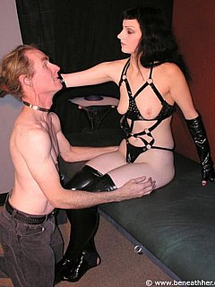 Mistress is sexy BDSM harness pushes male slave down to take his place underneath her
