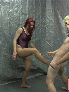 Two sporty sluts are holding a man tight while their mate is kicking him in the balls very hard