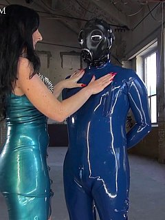 Lady is wearing rubber mini-dress herself and put on full-body rubber clothing onto her slave making outfit complete with the gas mask