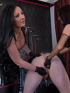 Femdom bitch is teaching younger mistress the proper way of fisting a man and then degrading him using strap-on toy