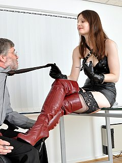 Secretary-dominatrix is wearing knee-boots and leather lingerie and punishes boss right in his office