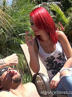 Mother and daughter are both smoking and spitting femdom slave into the mouth